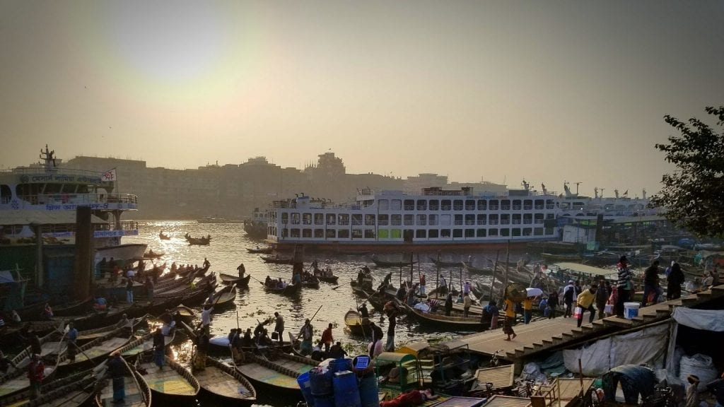 The sun is setting in the bustling Buriganga river in Dhaka, Bangladesh