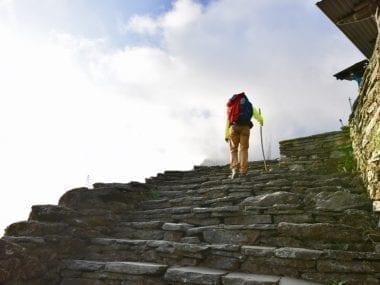 A trekker climbing stairs in Annapurna