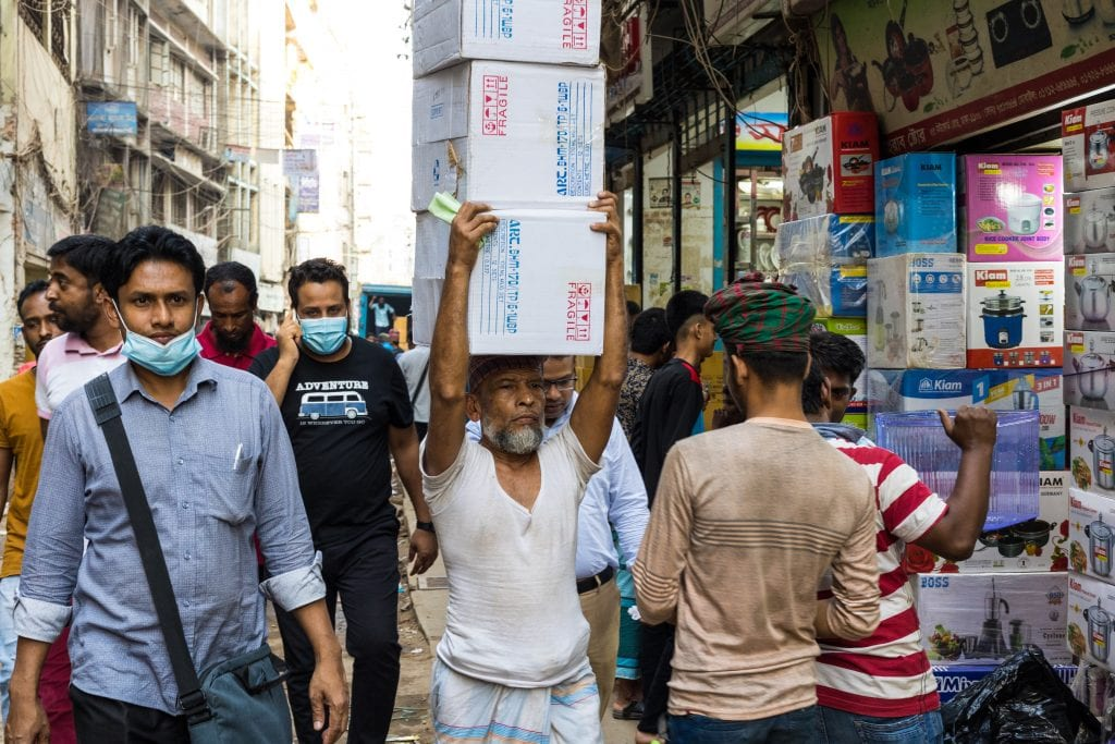 Old man carrying object in old Dhaka